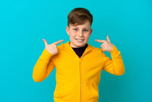Маленький рыжий мальчик, изолированные на синем фоне, показывает палец вверх