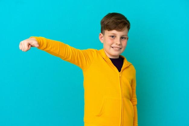 제스처를 엄지손가락을 포기 하는 파란색 배경에 고립 된 작은 빨간 머리 소년