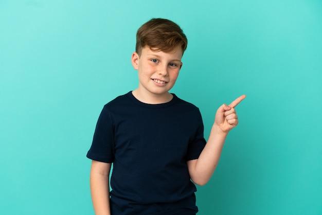 Маленький рыжий мальчик, изолированные на синем фоне, счастлив и указывая вверх