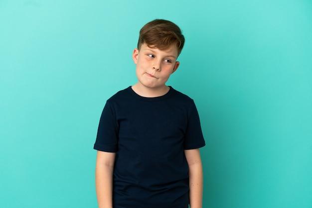 Маленький рыжий мальчик, изолированные на синем фоне, сомневаясь, глядя вверх
