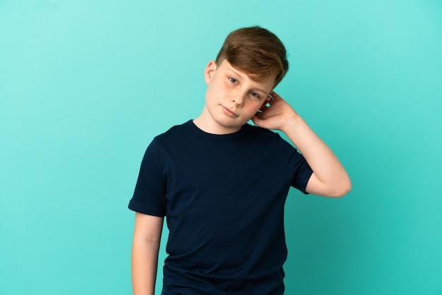 Маленький рыжий мальчик, изолированные на синем фоне, сомневаясь