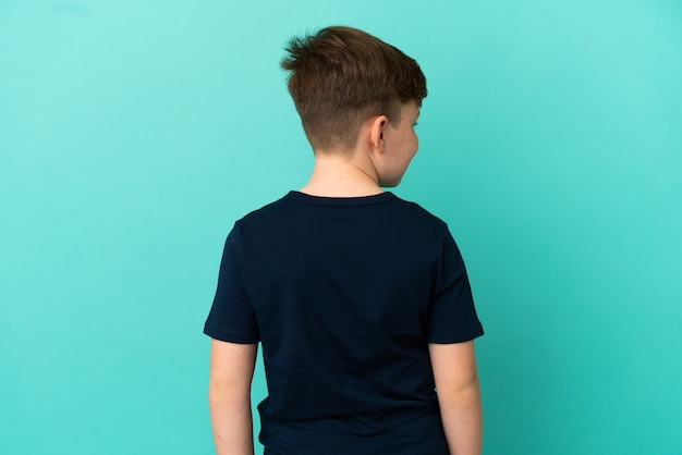 Маленький рыжий мальчик изолирован на синем фоне в заднем положении и смотрит в сторону