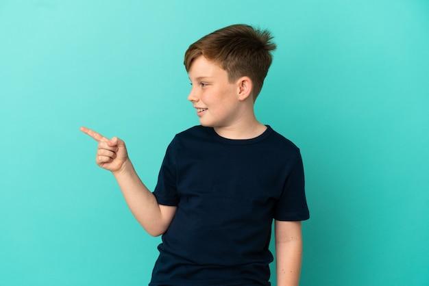 Маленький рыжий мальчик изолирован на синем фоне, намереваясь понять решение, подняв палец вверх