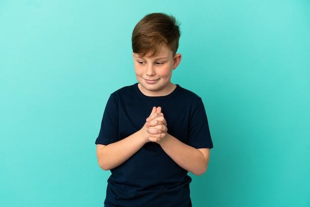 Маленький рыжий мальчик, изолированные на синем фоне смеясь
