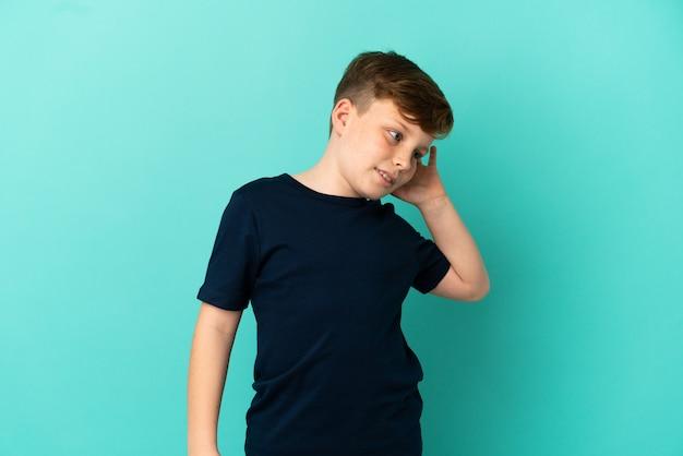 파란색 배경에 격리된 작은 빨간 머리 소년은 귀에 손을 대고 무언가를 듣고 있습니다.