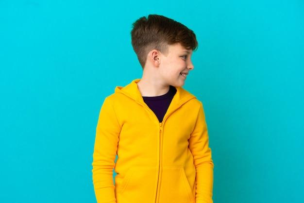 Маленький рыжий мальчик, изолированные на синем фоне, глядя в сторону
