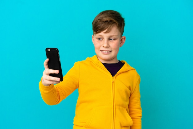 Маленький рыжий мальчик, изолированные на синем фоне, делая селфи