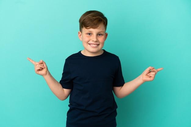 Маленький рыжий мальчик изолирован на синем фоне, указывая пальцем на боковые стороны и счастливым
