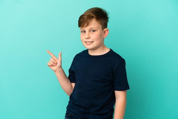 Маленький рыжий мальчик, изолированные на синем фоне, указывая пальцем в сторону