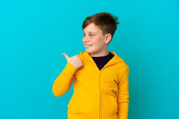 제품을 제시하기 위해 측면을 가리키는 파란색 배경에 고립 된 작은 빨간 머리 소년