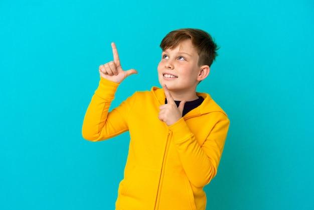 검지 손가락으로 가리키는 파란색 배경에 고립 된 작은 빨간 머리 소년 좋은 아이디어