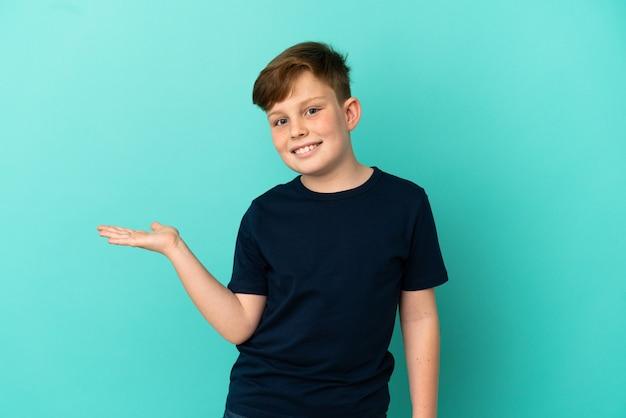 Маленький рыжий мальчик, изолированные на синем фоне, представляя идею, улыбаясь в сторону