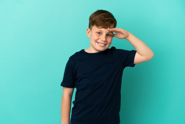 Маленький рыжий мальчик изолирован на синем фоне, салютуя рукой с счастливым выражением лица