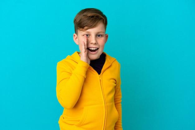 Маленький рыжий мальчик, изолированные на синем фоне, кричит с широко открытым ртом