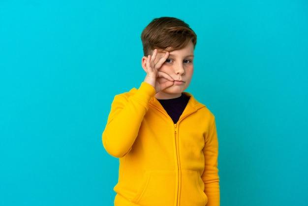 Маленький рыжий мальчик изолирован на синем фоне, показывая знак жеста молчания
