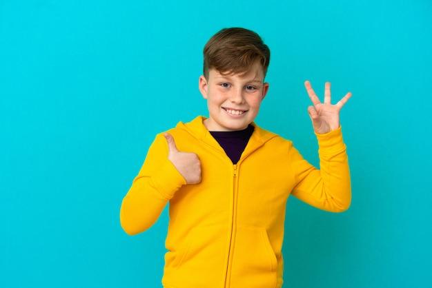 확인 표시와 제스처를 보여주는 파란색 배경에 고립 된 작은 빨간 머리 소년