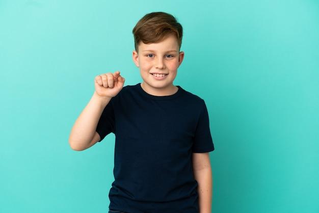 파란색 배경에 고립 된 작은 빨간 머리 소년 놀고 앞을 가리키는