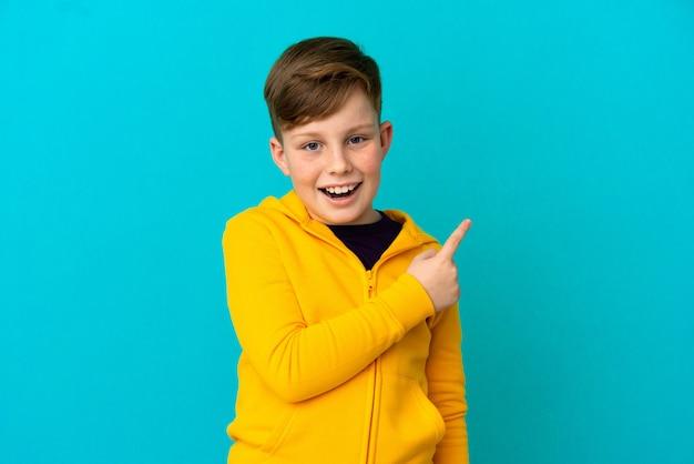 파란색 배경에 고립 된 작은 빨간 머리 소년 놀고 가리키는 측면