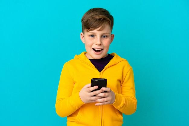 파란색 배경에 격리된 작은 빨간 머리 소년은 놀라고 메시지를 보냅니다.