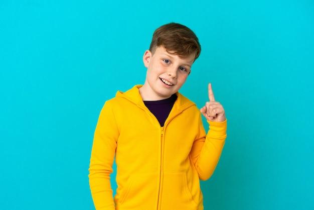 파란색 배경에 격리된 작은 빨간 머리 소년은 손가락을 가리키는 아이디어를 생각하고 있습니다.