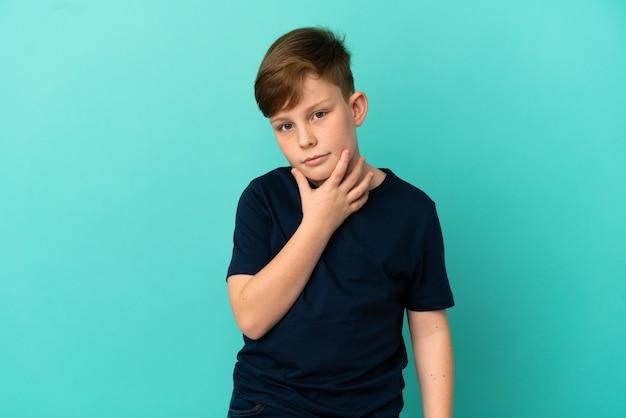 파란색 배경 및 생각에 고립 된 작은 빨간 머리 소년