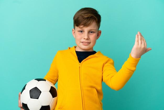 Маленький рыжий мальчик изолирован на синем фоне с футбольным мячом и делает приближающийся жест
