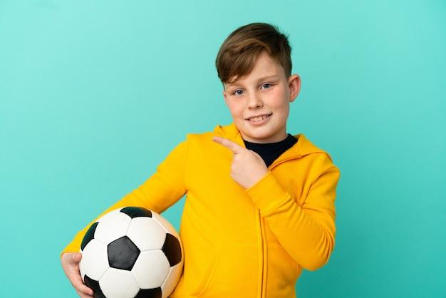 Маленький рыжий мальчик изолирован на синем фоне с футбольным мячом и указывает на боковой