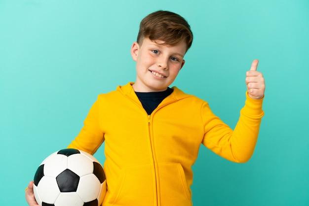 Маленький рыжий мальчик, изолированные на синем фоне с футбольным мячом и с большим пальцем вверх