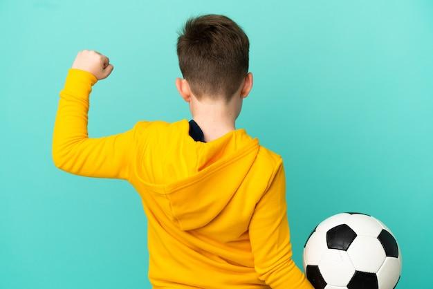 Маленький рыжий мальчик, изолированные на синем фоне с футбольным мячом