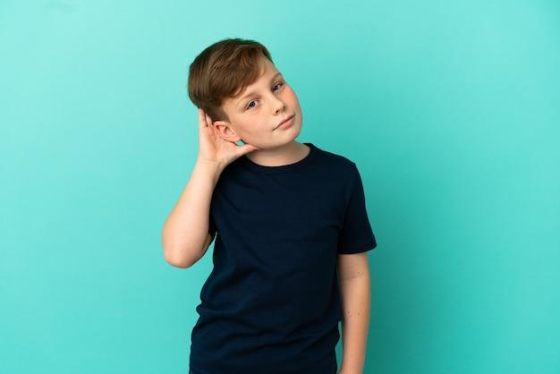 귀에 손을 넣어 뭔가를 듣고 파란색 표면에 고립 된 작은 빨간 머리 소년