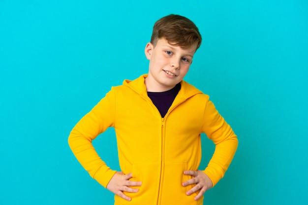 엉덩이에 팔을 포즈와 미소 파란색 벽에 고립 된 작은 빨간 머리 소년