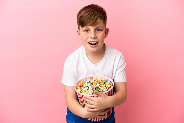 ポップコーンの大きなバケツを保持しているピンクの背景に分離された小さな赤毛の少年