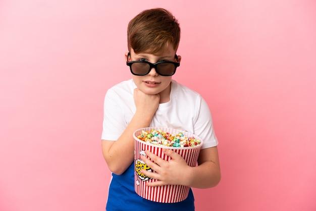Маленький рыжий мальчик изолирован на розовом фоне в 3d-очках и держит большое ведро попкорна