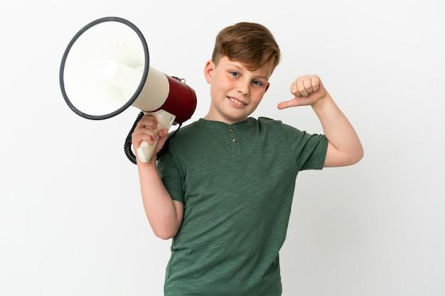 흰색 배경에 격리된 작은 빨간 머리 소년은 확성기를 들고 자랑스럽고 자기 만족했습니다.