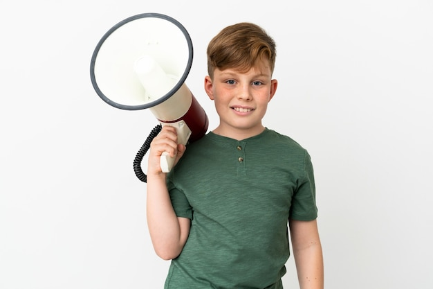 흰색 배경에 격리된 작은 빨간 머리 소년은 확성기를 들고 많이 웃고 있습니다.