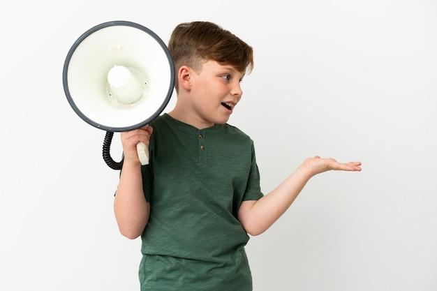 흰색 배경에 격리된 작은 빨간 머리 소년은 확성기를 들고 놀란 표정으로