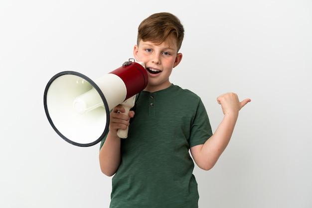 Маленький рыжий мальчик, изолированные на белом фоне, кричит в мегафон и указывает сторону