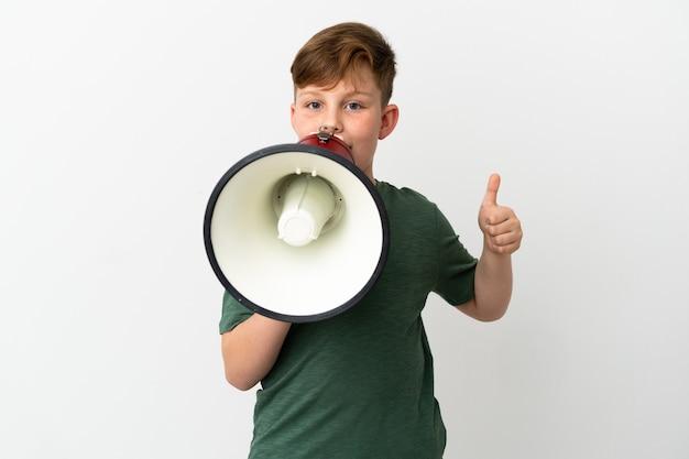 흰색 배경에 격리된 작은 빨간 머리 소년은 확성기를 통해 무언가를 발표하고 엄지손가락을 치켜들고 소리를 지릅니다.