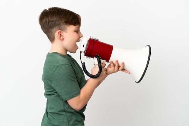 Маленький рыжий мальчик на белом фоне кричит в мегафон, чтобы объявить что-то в боковом положении