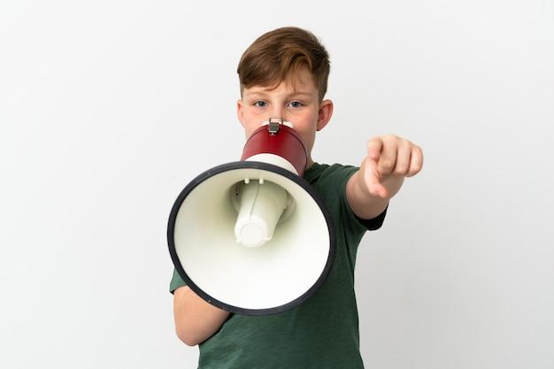 흰색 배경에 격리된 작은 빨간 머리 소년은 전면을 가리키면서 무언가를 발표하기 위해 확성기를 통해 외쳤다