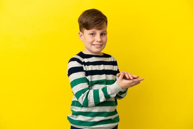 노란색 배경 박수에 고립 된 작은 빨간 머리 소년