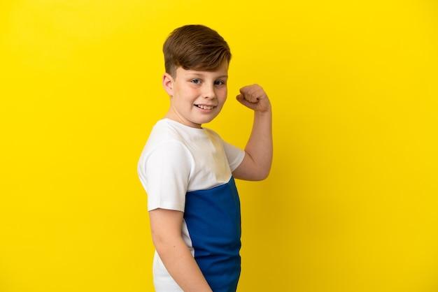 승리를 축하하는 노란색 배경에 고립 된 작은 빨간 머리 소년