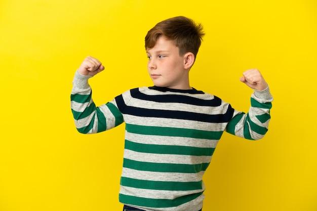 Маленький рыжий мальчик, изолированные на желтом фоне, делает сильный жест
