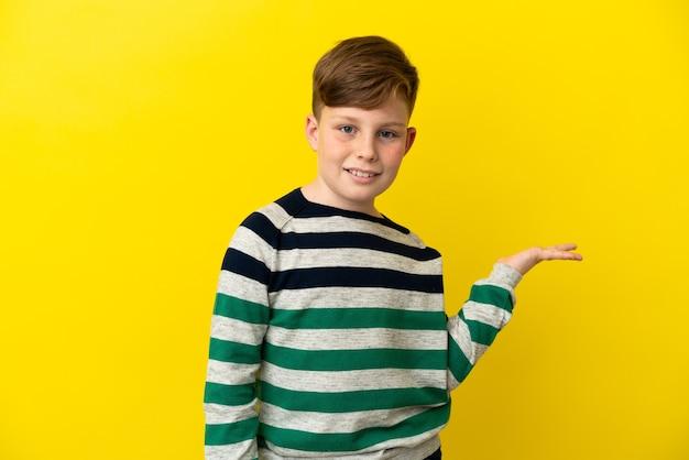 Маленький рыжий мальчик изолирован на желтом фоне, держа на ладони воображаемое пространство, чтобы вставить рекламу