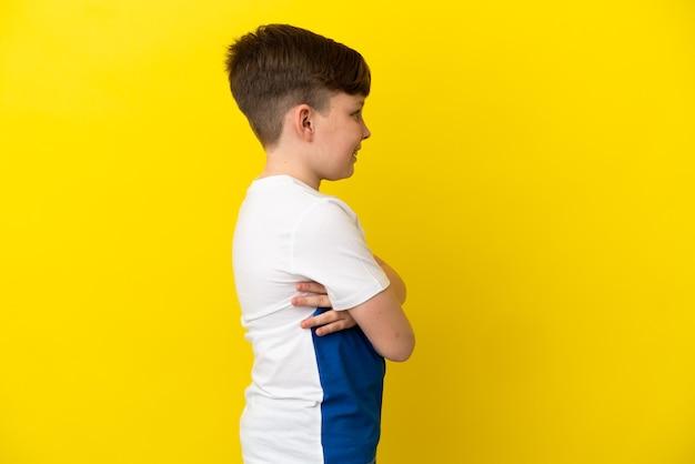 Маленький рыжий мальчик, изолированные на желтом фоне в боковом положении