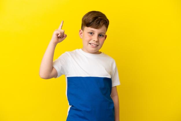 Маленький рыжий мальчик изолирован на желтом фоне, намереваясь понять решение, подняв палец вверх