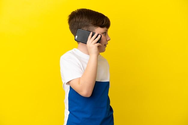 노란색 배경에 격리된 작은 빨간 머리 소년은 휴대전화와 대화를 유지하고 있습니다.