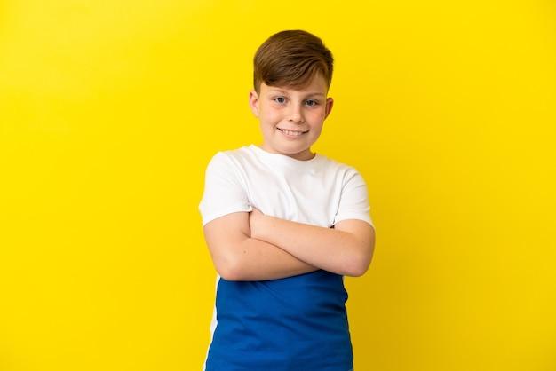 Маленький рыжий мальчик изолирован на желтом фоне, скрестив руки в лобном положении