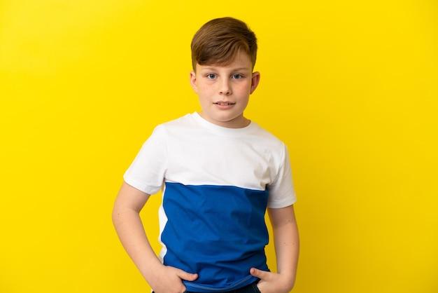 Маленький рыжий мальчик, изолированные на желтом фоне смеясь Premium Фотографии