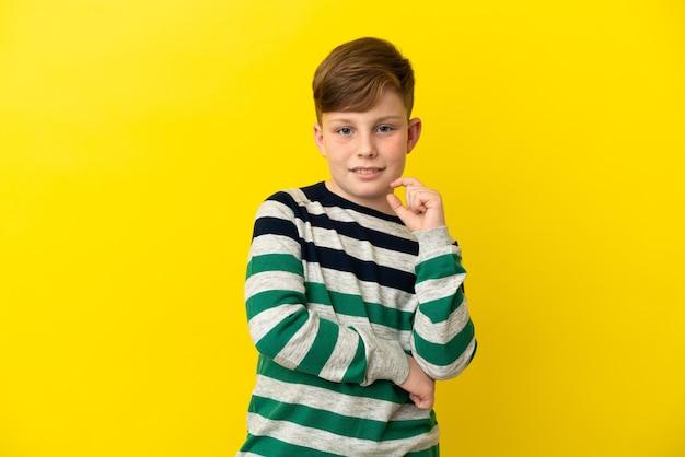 노란색 배경 웃음에 고립 된 작은 빨간 머리 소년